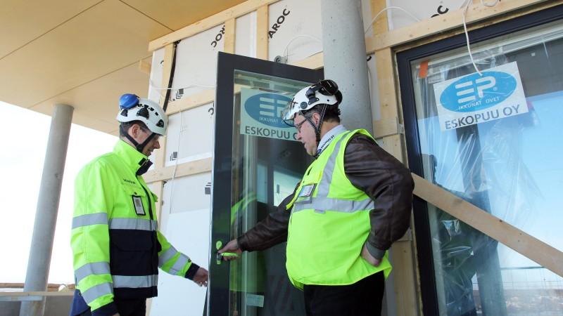 Skanskan hankintapäällikkö Jaakko Holopainen ja Eskopuun projektipäällikkö Hannu Ikäheimo tarkastelevat parvekkeen oven asennusta As Oy Oulun Pajarinkulmassa keväällä 2016.